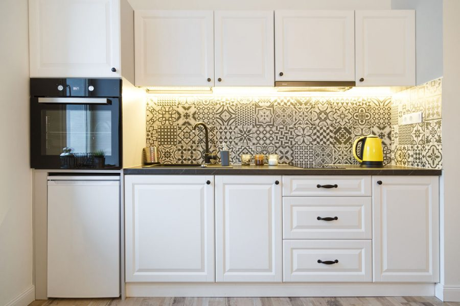 Beautiful home kitchen with white cabinets and backlight.